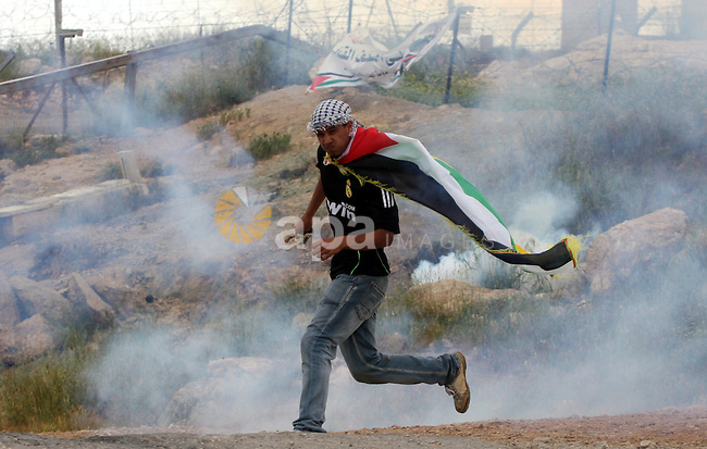 A Palestinian protester runs for cover from tear gas canisters fired by Israeli soldiers during the weekly demonstration against Israel's controversial separation barrier in the village of Bilin, near the West Bank city of Ramallah on April 22, 2011. Some 250 left-wing Israeli and foreign activists protested in the West Bank village of Bilin against the separation fence being built in the area. Some of the protestors hurled stones at the security forces, who used crowd dispersal means in response. Photo by Issam Rimawi