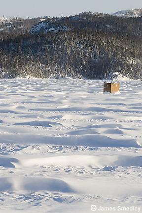 Ice fishing hut on a windy frozen lake