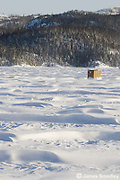 Ice fishing hut on a windy frozen lake
