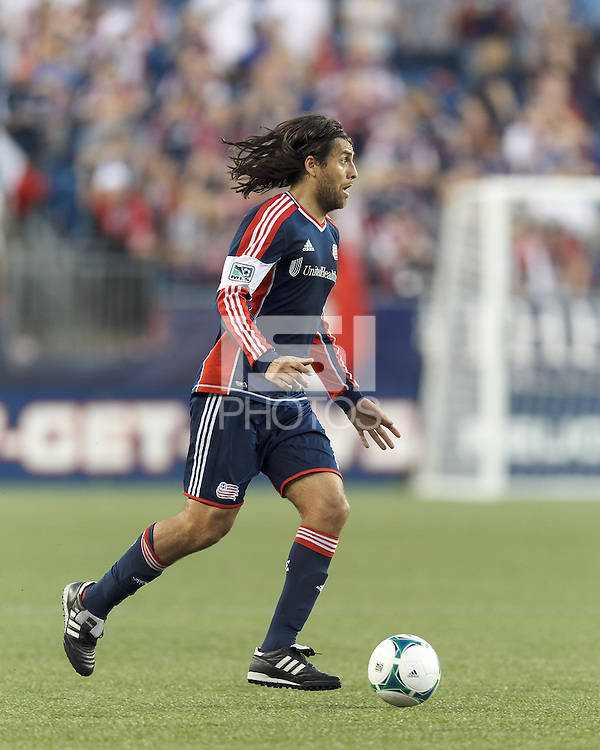 New England Revolution midfielder Juan Carlos Toja (7) dribbles at midfield.  In a Major League Soccer (MLS) match, the New England Revolution (blue) tied D.C. United (white), 0-0, at Gillette Stadium on June 8, 2013.