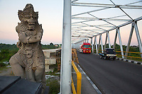 Bali, Indonesia.  Mythical Figure Guards a Bridge in Southern Bali.  New Bridge under Construction in Background.