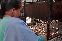 Kathmandu, Nepal.  Nepali Lady Lights a Candle at a Shrine adjacent to the Manu Ganesh (Ashok Binayak) Shrine, Durbar Square.