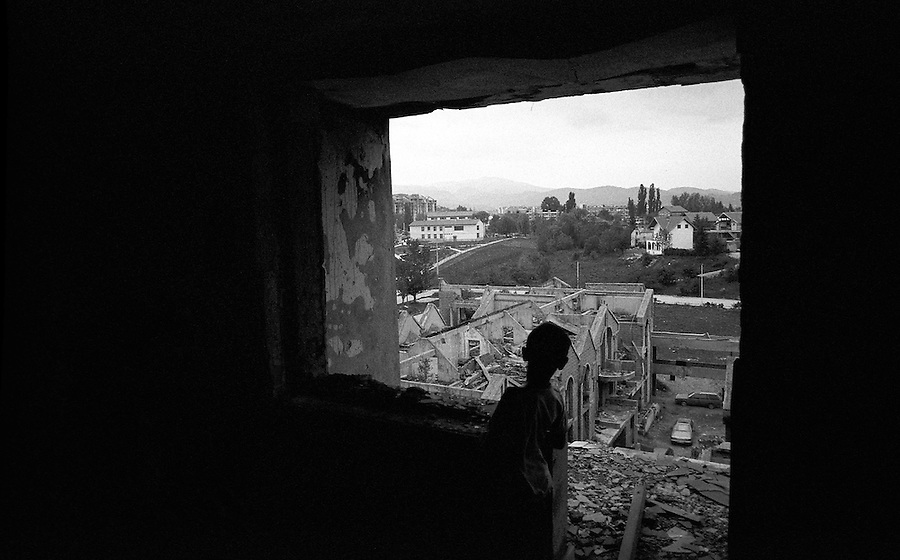 A boy looks out from a fifth floor balcony across to what would have been the Serb lines during the siege.