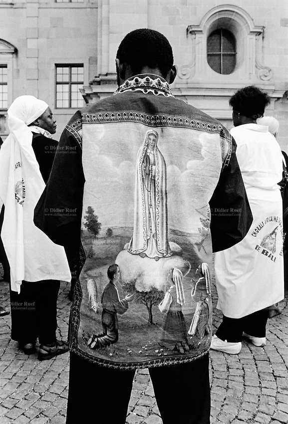 "Switzerland. Canton Schwyz. Einsiedeln Abbey. African pilgrimage. Various religious african communities coming from allover Switzerland and southern Germany celebrate their faith and belief in Jesus Christ. A black man wears a shirt with drawing of ""Our Lady of Fátima "" a title for the Virgin Mary due to her reputed apparitions to three shepherd children at Fátima, Portugal in 1917. The title of Our Lady of the Rosary is also sometimes used to refer to the same apparition. According to religious tradition, Mary was an Israelite Jewish woman and the mother of Jesus. Among her many other names and titles are the Virgin Mary or Blessed Virgin Mary, Mother of God, and Saint Mary in Western churches, Theotokos in Orthodox Christianity, and Maryam, mother of Isa in Islam. Einsiedeln Abbey is a Benedictine monastery in the town of Einsiedeln. The abbey is dedicated to Our Lady of the Hermits, the title being derived from the circumstances of its foundation, for the first inhabitant of the region was Saint Meinrad, a hermit. It is a territorial abbey and, therefore, not part of a diocese, subject to a bishop. It has been a major resting point on the Way of St. James for centuries. 31.08.13 © 2013 Didier Ruef"