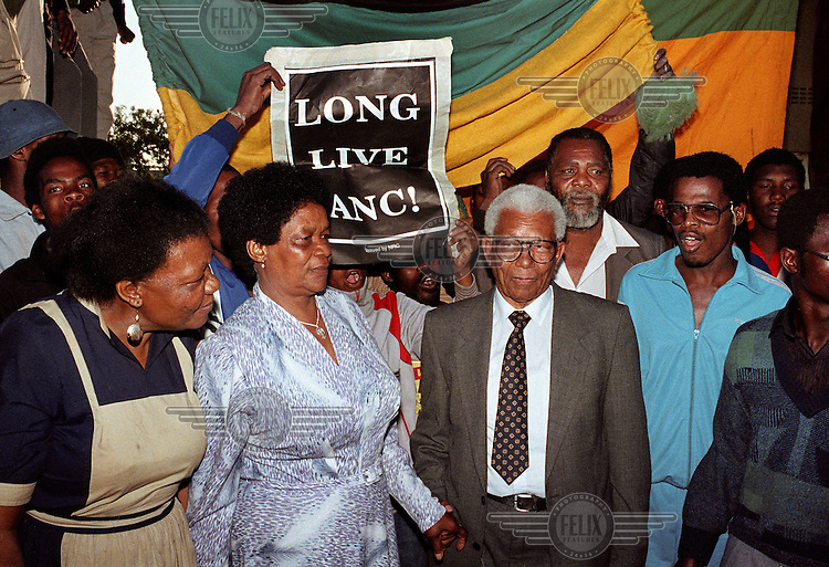 Walter Sisulu (right centre) of the African National Congress (ANC) with his wife Albertina after his release from prison. He had just arrived back in Soweto. Behind them a person holds up a poster which reads: 'Long Love ANC!'.