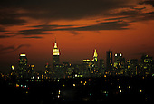 New York, USA. Skyline of uptown Manhattan with Empire State Building and Chrysler Building at sunset with orange sky.