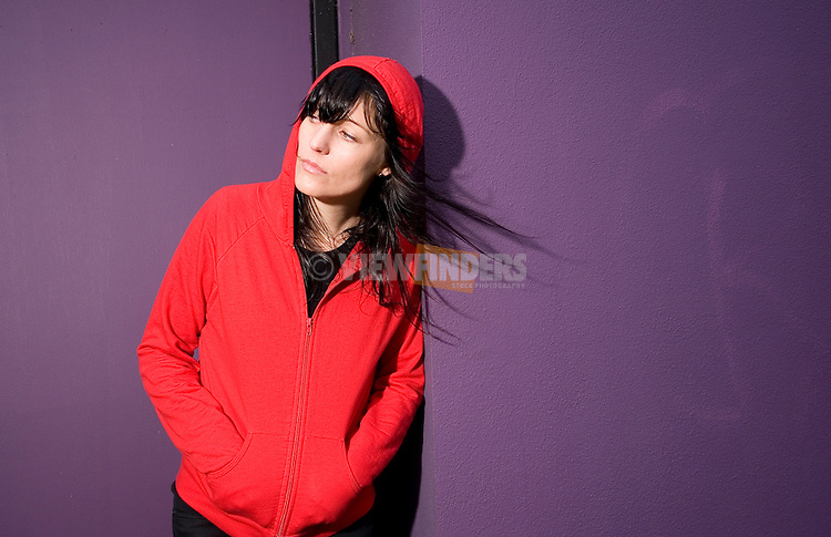 Woman in red leaning against a purple wall.