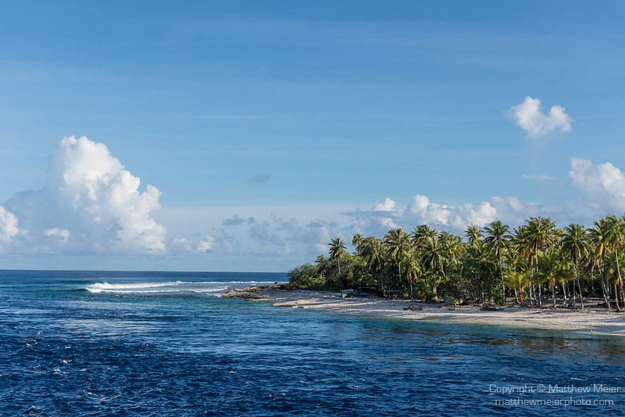 Apataki Atoll, Tuamotu Archipelago, French Polynesia; view of  the palm tree covered island bordering one side of Tehere Pass from inside the channel on Apataki Atoll