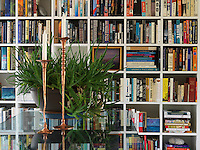 Detail of candlesticks and a succulent on the library table in front of a well-stocked bookcase