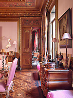 A grand sitting room, decorated in pastel pink, with gilded mouldings and parquet flooring. Two lamps and other items are displayed on an elegant antique chest of drawers.