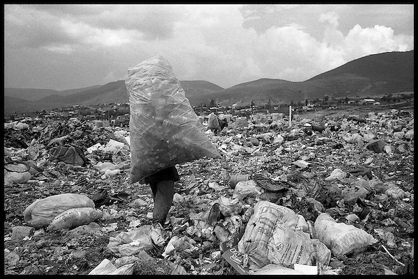 Oaxaca city dump, Oaxaca, Mexico. A plastic collector carries her load. The water shortage in the city greatly adds to the amount of plastic water bottles thrown away. The bottles are collected from garbage bags at the dump and sold to a company for recycling....