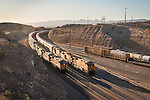 A BNSF railway intermodal stack train passes a stopped BNSF auto carrier train at the east end of the rail yard, Barstow, Calif.