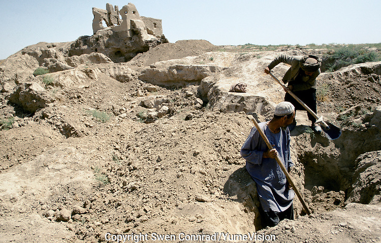 Two local farmer dig to find some antiquity at the Tilia Tepe archaeological site near Sheberghan, North west of Afghanistan. In 1996 the site was mechanically excavated by bulldozer under the command of the Afghan Uzbek commander General Rashid Dostum.The Russian Victor Sariyiannidis discovered more them 20,000 pieces of gold jewellery in 1979 in Tilia Tepe in Afghanistan  an area once occupied by the Hellenistic state of Bactria (Bactriana).