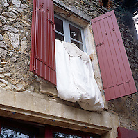 A white duvet hangs out of a window with red painted shutters.