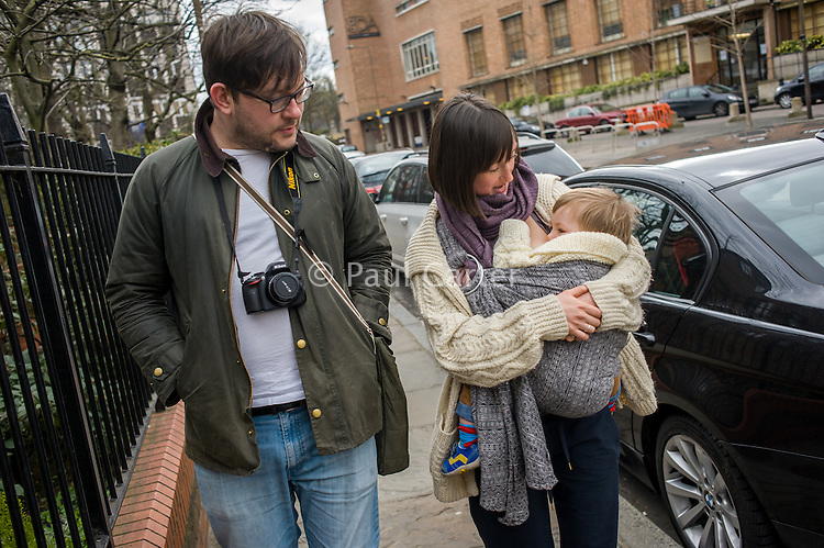 A mother breastfeeds her 15 month old boy from a sling while walking along a city pavement with her partner.<br /> <br /> London, England, UK<br /> 22-03-2015<br /> <br /> &copy; Paul Carter / wdiip.co.uk