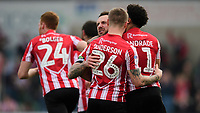 Lincoln City's Neal Eardley celebrates scoring his side's equalising goal to make the score 1-1 with team-mates Harry Anderson, centre, and Bruno Andrade, right<br /> <br /> Photographer Chris Vaughan/CameraSport<br /> <br /> The EFL Sky Bet League Two - Lincoln City v Macclesfield Town - Saturday 30th March 2019 - Sincil Bank - Lincoln<br /> <br /> World Copyright © 2019 CameraSport. All rights reserved. 43 Linden Ave. Countesthorpe. Leicester. England. LE8 5PG - Tel: +44 (0) 116 277 4147 - admin@camerasport.com - www.camerasport.com