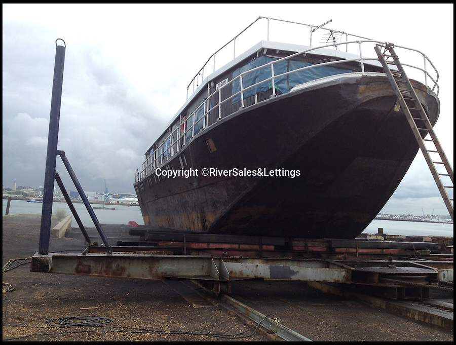 BNPS.co.uk (01202 558833)<br /> Pic: RiverSales&amp;Lettings/BNPS<br /> <br /> ****Please use full byline****<br /> <br /> The barge during the refurbishment.<br /> <br /> A 100-year-old barge once used to ship cargo up and down the River Thames has been transformed into a plush four-bedroom house that is now on the market for &pound;450,000.<br /> <br /> The 90ft boat was salvaged from the banks of Thames in the 1970s and turned into a floating dormitory for schoolchildren at an outdoor activity centre.<br /> <br /> But it has since been given a complete makeover and now looks more like a cosy country cottage than a boat.<br /> <br /> The two-storey houseboat runs off mains electricity, has wifi access, electric heating, and hot water, and it also has a reserve water tank stored in its funnel.<br /> <br /> And buyers can count the picturesque River Hamble near Southampton, Hants, as their back garden.