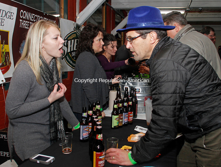 Winsted, CT-011814MK12 Lisa Bielawski, from Thomas Hooker Brewery, describes a beer selection to YMCA board member Tom Filippini during the first annual Pints for a Purpose beer tasting and a concert to benefit the Northwest YMCA's Strong Kids campaign at Whiting Mills Saturday night in Winsted. Winsted YMCA branch director Jay Cohen said over a hundred beer enthusiasts came to enjoy seventeen local breweries and the proceeds will benefit the local community and families in need. Michael Kabelka / Republican-American
