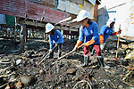 Maryglen Roa (left), Maryann Lloveras and Jeanette Ayo clean up debris in Tacloban, a city in the Philippines province of Leyte that was hit hard by Typhoon Haiyan in November 2013. The storm was known locally as Yolanda. They are participants in a United Nations funded cash for work program.
