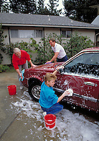 CAUCASIAN THREE GENERATIONS OF MEN WASHING THE FAMILY CAR. CAUCASIAN FAMILY. OAKLAND CALIFORNIA.