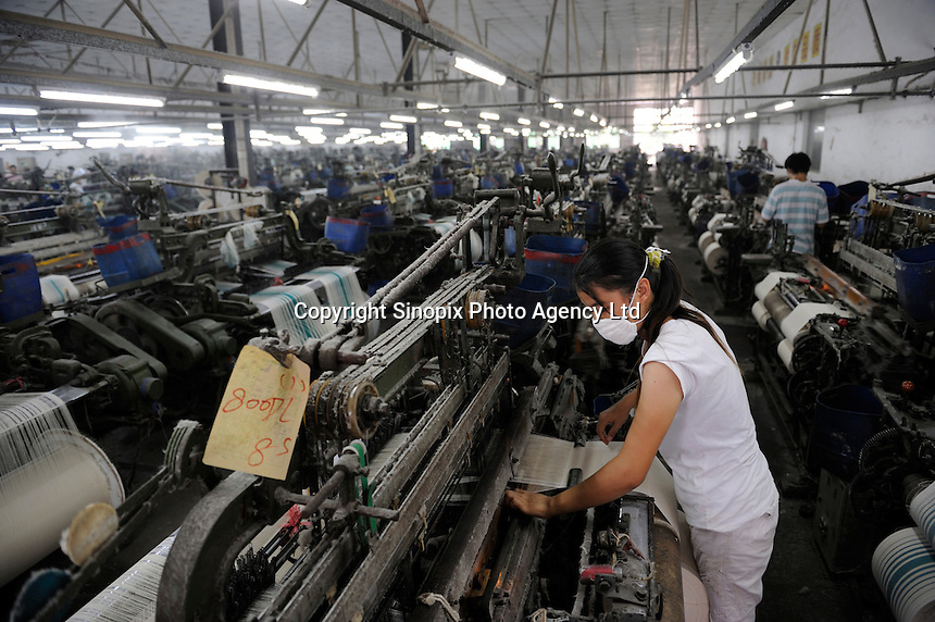 Female worker operating machine at a textile factory in Dongguan, Guangdong, China..