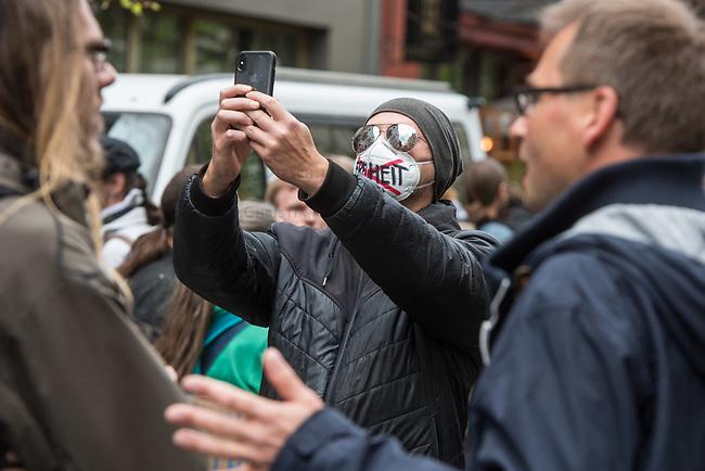 """Auf und rund um den Rosa-Luxemburg-Platz in Berlin-Mitte haben am Samstag den 25. April 2020 mehrere hundert Menschen gegen die Einschraenkungen im Zuge der Massnahmen zur Eindaeemung der Covid-19-Pandemie protestiert. Rechtsextremisten, Hooligans, Antisemiten, Verschwoerungstheoretiker und AfD-Politiker hatten zu einer sogenannten """"Hygiene-Demo"""" versammelt. Vereinzelt protestierten Menschen am Rande gegen diese Demonstration.<br /> Die Polizei war mit mehreren hundert Beamten im Einsatz und nahm mehr als 100 Personen fest.<br /> Im Bild: EIn Demonstrant traegt eine Mund-Nase-Schutzmaske, auf der er das Wort """"Freiheit"""" durchgestrichen hat und macht ein Selfie von sich in der ungenehmigten Demonstration.<br /> 25.4.2020, Berlin<br /> Copyright: Christian-Ditsch.de<br /> [NUR FUER REDAKTIONELLE ZWECKE! Werbung nur auf Anfrage beim Fotografen. Inhaltsveraendernde Manipulation des Fotos nur nach ausdruecklicher Genehmigung des Fotografen. Vereinbarungen ueber Abtretung von Persoenlichkeitsrechten/Model Release der abgebildeten Person/Personen liegen nicht vor. NO MODEL RELEASE! Don't publish without copyright Christian-Ditsch.de, Veroeffentlichung nur mit Fotografennennung, sowie gegen Honorar, MwSt. und Beleg. Konto: I N G - D i B a, IBAN DE58500105175400192269, BIC INGDDEFFXXX, Kontakt: post@christian-ditsch.de<br /> Bei der Bearbeitung der Dateiinformationen darf die Urheberkennzeichnung in den EXIF- und  IPTC-Daten nicht entfernt werden, diese sind in digitalen Medien nach §95c UrhG rechtlich geschuetzt. Der Urhebervermerk wird gemaess §13 UrhG verlangt.]"""