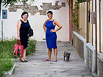 Women and cats, colorful village of Burano, Italy.
