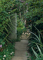 A short path densely planted on either side creates a sense of anticipation