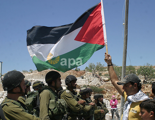 Israeli soldiers stand behind razor-wire and the Palestinian protester holds Palestinian flag during a demonstration against the construction of Israel's separation barrier  in the West Bank village of Maasarah near Bethlehem, Friday,June 5, 2009. Photo Najeh Hashlamoun