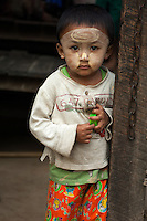 A small boy, well protected from the sun by a liberal application of the thanaka bark paste that many Burmese use to protect their skin, peers round the gatepost of his home in the fishing village of Jade Taw on the Bay of Bengal in Myanmar.