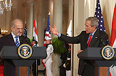 Washington, D.C. - June 24, 2005 -- United States President George W. Bush, right, gestures towards Prime Minister Ibrahim al-Jaafari of Iraq, left, during a joint press conference in the East Room at the White House in Washington, D.C. on June 24, 2005.  They discussed the re-building of Iraq and refused to give a time-table for the withdrawal of United States forces.<br /> Credit: Ron Sachs / CNP