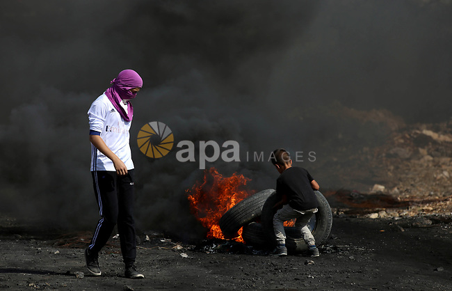 A Palestinian protester burns tires during clashes with Israeli security forces following a demonstration against the expropriation of Palestinian land by Israel in the village of Kfar Qaddum, near Nablus in the occupied West Bank, on October 20, 2017. Photo by Ayman Ameen