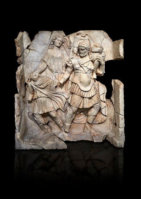 Roman Sebasteion relief  sculpture of Aineas' flight from Troy, Aphrodisias Museum, Aphrodisias, Turkey.   Against a black background.<br /> <br /> Aineas in armour carries his aged farther Anchises on his shoulders and leads his young son Lulus by his hand. They are fleeing from the sack of Troy. The figure floating behind is Aphrodite, Aineas' mother: she is helping their escape. Old Anchises carries a round box that held images of Troy's ancestral gods.