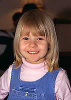 Smiling girl age 4 in blue jumper.  Brooklyn Center  Minnesota USA