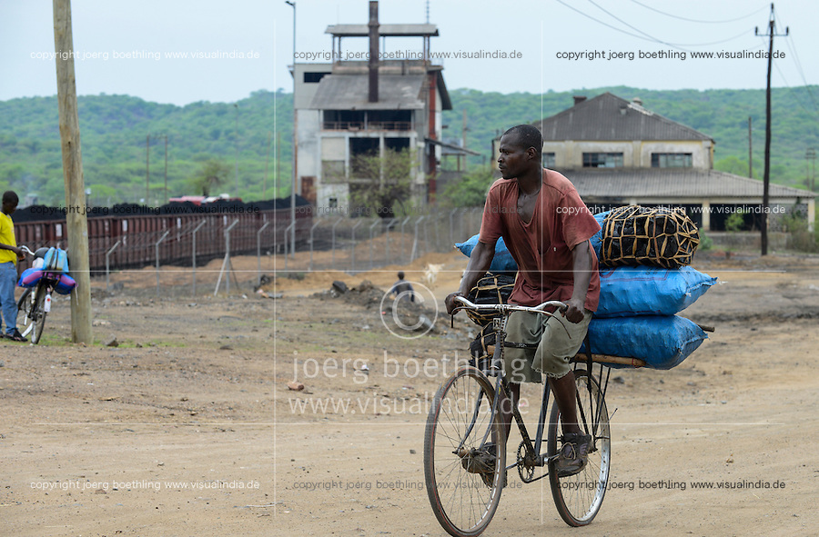 MOZAMBIQUE, Moatize, local transport char coal with bicycle, behind coal terminal of Jindal Africa a indian company, coal is transported by railway to port Beira for export / MOSAMBIK, Moatize, Transport von Holzkohle mit Fahrrad, Hintergrund Kohleverladeterminal von Jindal Africa, ein indisches Unternehmen, die Kohle wird von hier per Bahn fuer den Export zum Hafen Beira transportiert