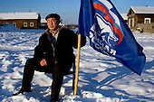 Nikifor Alfonski, head of the Bedime village in Yakutia, holds a United Russia flag. Alfonski is pushing fellow villagers to join the party, which backs Russian President Vladimir Putin. .On one single day this year, 136 people in his village joined the party. .United Russia is a political party in the Russian Federation which usually labels itself centrist. It can be seen as Putin's vehicle in the State Duma (the lower house of Russian parliament). It was founded in April 2001 as a merger between Yuriy Luzhkov's, Yevgeny Primakov's and Mintimer Shaeymiev's Fatherland - All Russia party, and the Unity Party of Russia, led by Sergei Shoigu and Alexander Karelin..United Russia is a relatively new party in the Russian Parliament but has been making great gains in recent federal and local elections due to the popularity of Putin.
