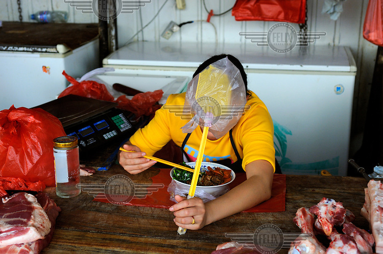 Woman working on a butcher's stand, eating lunch holding a fly swat at a city market.