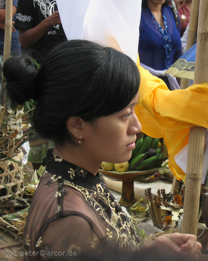 woman watching cremation ceremonies in Tampak Siring, village of horn carving art, central Bali, archipelago Indonesia, August 2009