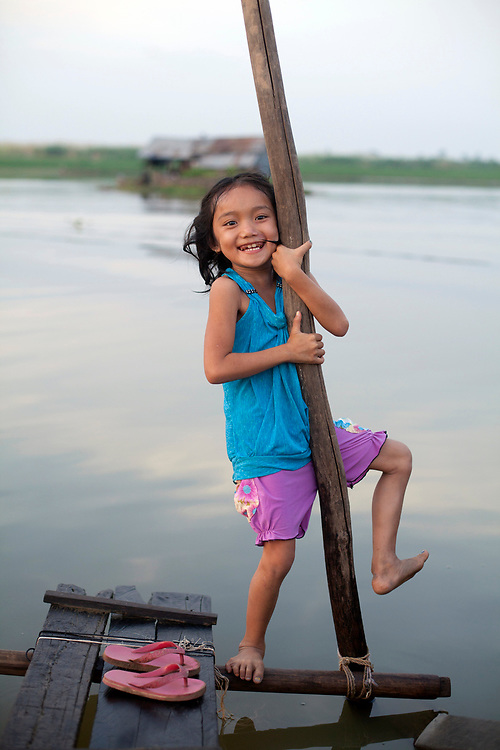 A young girl plays by  the river in a small village outside of Phnom Penh, Cambodia. <br /> <br /> Photos &copy; Dennis Drenner 2013.