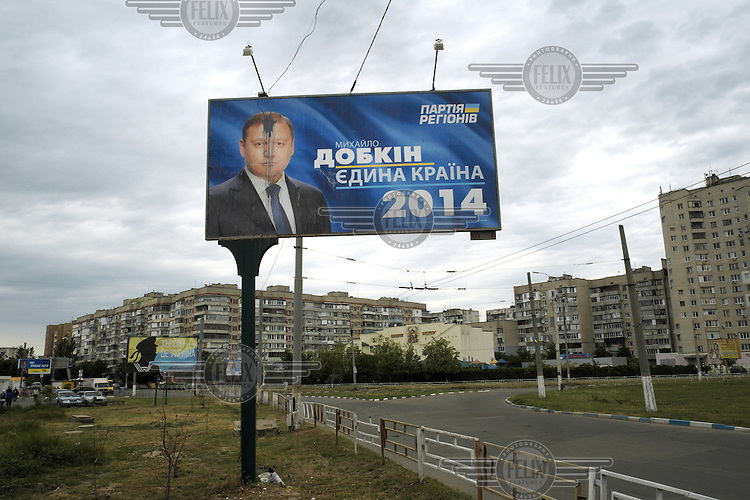 A billboard advertisement for the Ukrainian presidential candidate Mikhail Dobkin is defaced by paint in Kherson.