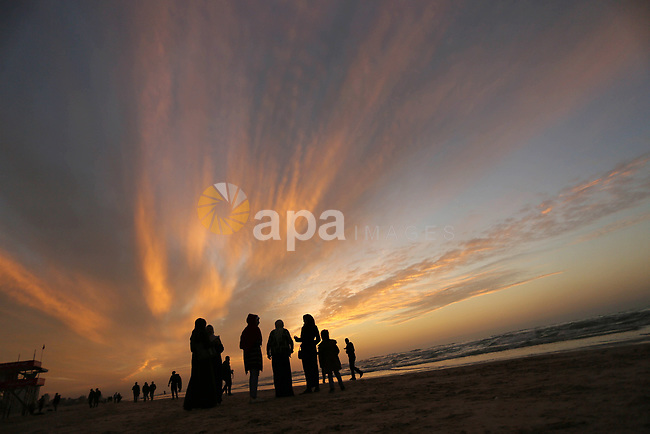 Palestinians walk at the beach during sunset in Gaza City on January 3, 2018. Photo by Ashraf Amra