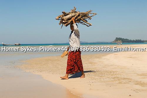 Ngapali Beach Southern Rakhaing state. Woman carrying fire wood back to Jade Taw fishing village.
