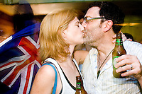 Australia fans Leonie Carmen and husband David Carmen share a kiss in celebration of their team's tie with Croatia in a World Cup match that advanced them to the next round on June 22, 2006 at the Sunburnt Cow, a bar in New York City.<br /> <br /> The World Cup, held every four years in different locales, is the world's pre-eminent sports tournament in the world's most popular sport, soccer (or football, as most of the world calls it).  Qualification for the World Cup is open to any country with a national team accredited by FIFA, world soccer's governing body. The first World Cup, organized by FIFA in response to the popularity of the first Olympic Games' soccer tournaments, was held in 1930 in Uruguay and was participated in by 13 nations.    <br /> <br /> As of 2010 there are 208 such teams.  The final field of the World Cup is narrowed down to 32 national teams in the three years preceding the tournament, with each region of the world allotted a specific number of spots.  <br /> <br /> The World Cup is the most widely regularly watched event in the world, with soccer teams being a source of national pride.  In most nations, the whole country is at a standstill when their team is playing in the tournament, everyone's eyes glued to their televisions or their ears to the radio, to see if their team will prevail.  While the United States in general is a conspicuous exception to the grip of World Cup fever there is one city that is a rather large exception to that rule.  In New York City, the most diverse city in a nation of immigrants, the melting pot that is America is on full display as fans of all nations gather in all possible venues to watch their teams and celebrate where they have come from.