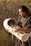 A young Native American Indian women with her baby in a cradle