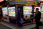A man buys a drink from vending machines in Tokyo, Japan on 29 April 2010. Photographer: Robert Gilhooly