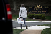 A woman holds a sign as she waits outside of the Trump National Golf Club in Sterling, Virginia, for United States President Donald J. Trump to leave on April 7, 2019 in Washington, DC. <br /> Credit: Oliver Contreras / Pool via CNP