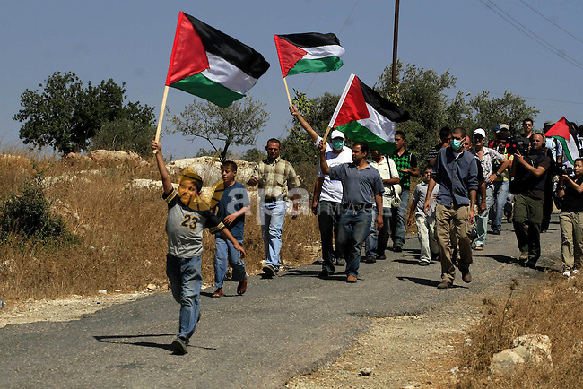 protesters wave a palestinian flag during a protest against the controversial Israeli barrier in the West Bank village of Bilin near Ramallah on Sep 25, 2009. Photo by Issam Rimawi