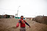 A boy plays with a deflated ball on Friday, Apr. 17, 2009 in Ventanilla, Peru.