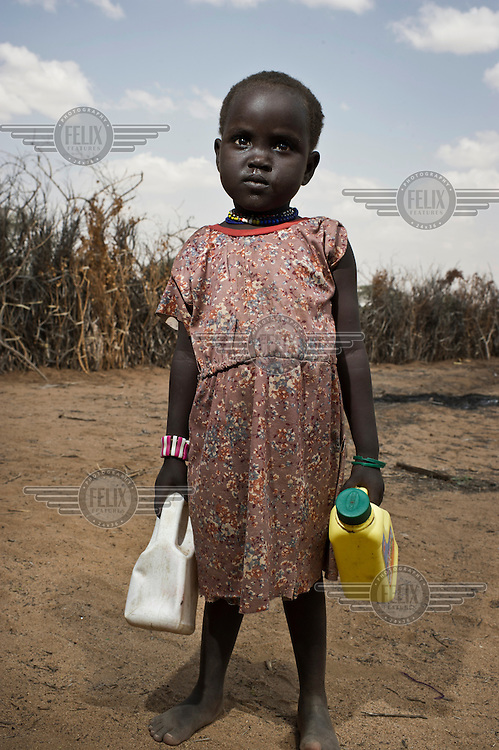 A young Turkana girl with plastic bottles filled with maize meal collected from a food distribution centre near Tiya. Turkana District has been worst affected in Kenya's most serious drought for 60 years.