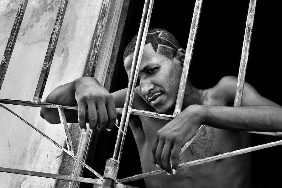 A young Cuban man stands behind the door grill during a hot summer afternoon, Santiago de Cuba, Cuba, 31 July 2008.